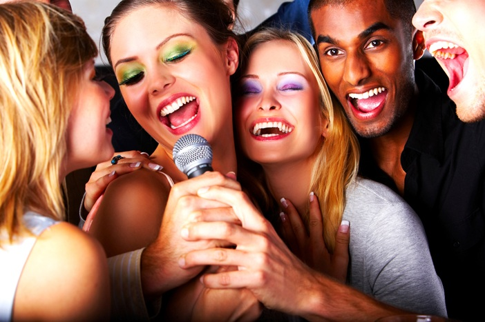 Five attractive friends singing together at a karaoke party