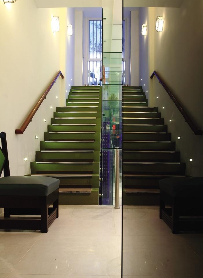 Trục cầu thang được chiếu sáng hợp lý bởi đèn LED dẫn dắt lối đi và đèn tường ánh sáng vàng dịu nhẹ