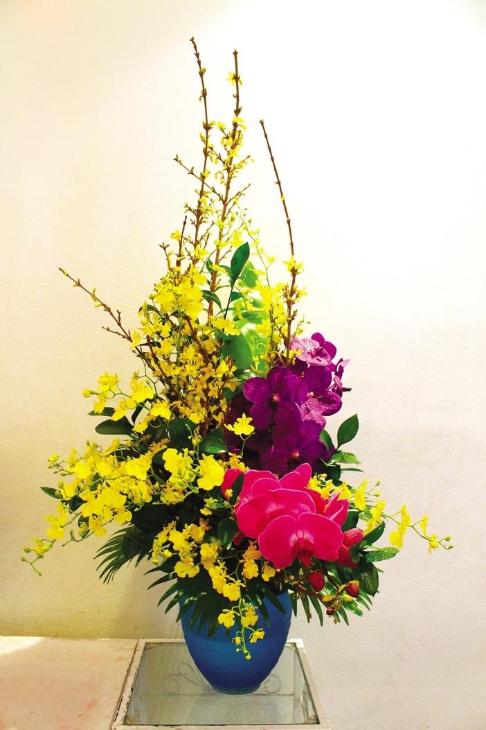Kết hợp lan hồ điệp, lan vũ nữ và hoa đầu xuân (hoa mai Mỹ) với màu vàng đặc trưng tết Việt