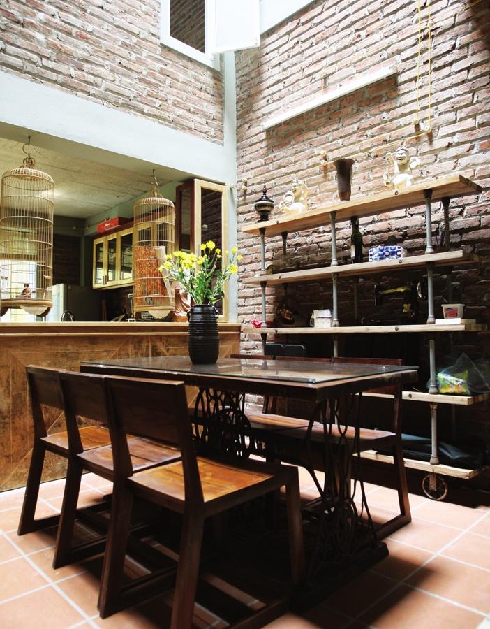 Sân trong cũng là giếng trời, nơi bày bàn ăn, phía sau là quầy bar với đôi lồng chim và bếp