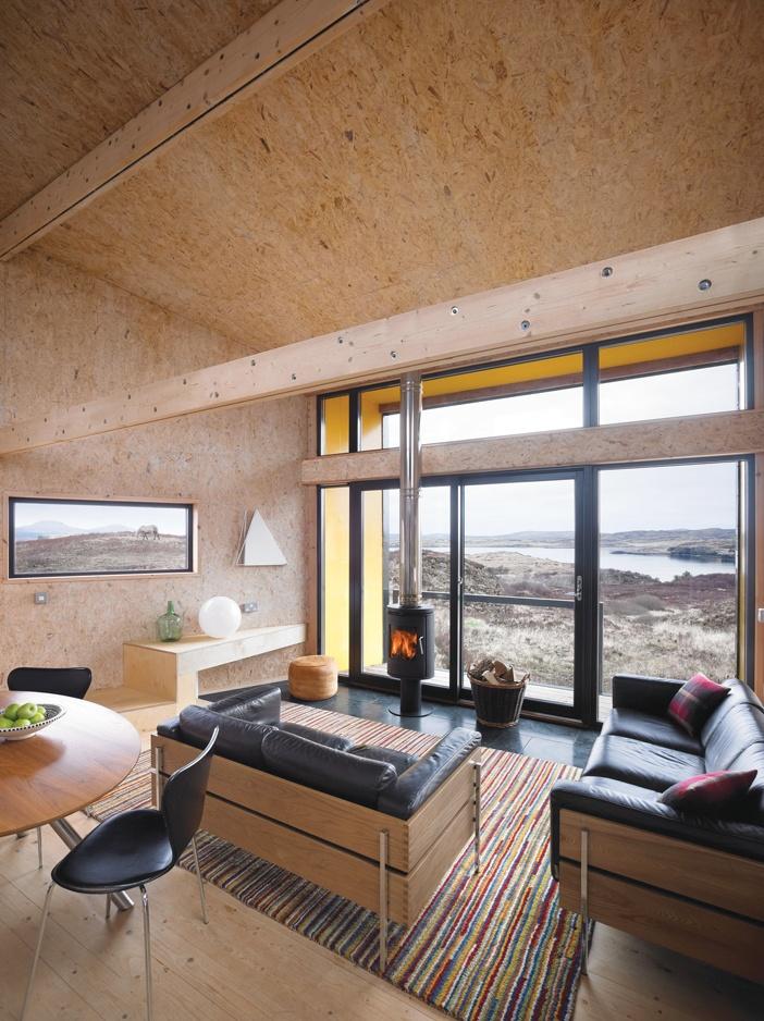 Phòng khách hướng bắc mở tầm nhìn ra mặt vịnh biển qua khung kính lớn, toàn bộ các vách được phủ ván ép, một lò sưởi nhỏ và hiện đại cho những ngày giá lạnh mùa đông
