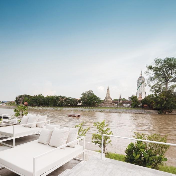 Khu vực thư giãn và nhà hàng ngoài trời, bên kia bờ sông là những đền tháp cổ kính của cố đô Ayutthaya với ngôi đền thiêng Putthai Sawan (cao, bên phải)