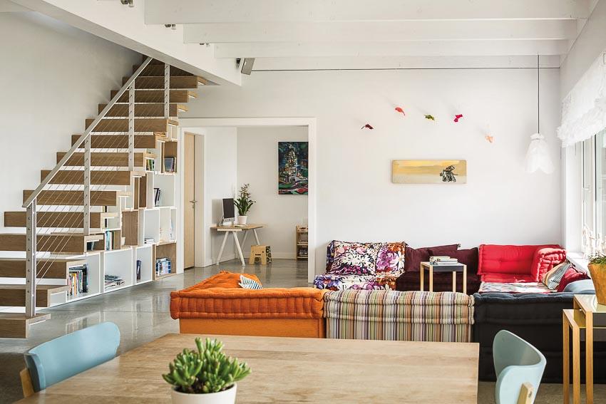 Phòng khách tầng trệt khu ở với bộ sofa đa sắc màu