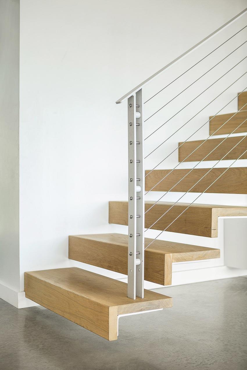 Cầu thang lên tầng trên được thiết kế thanh lịch với gỗ và thép sợi, bên dưới tận dụng làm kệ sách 1