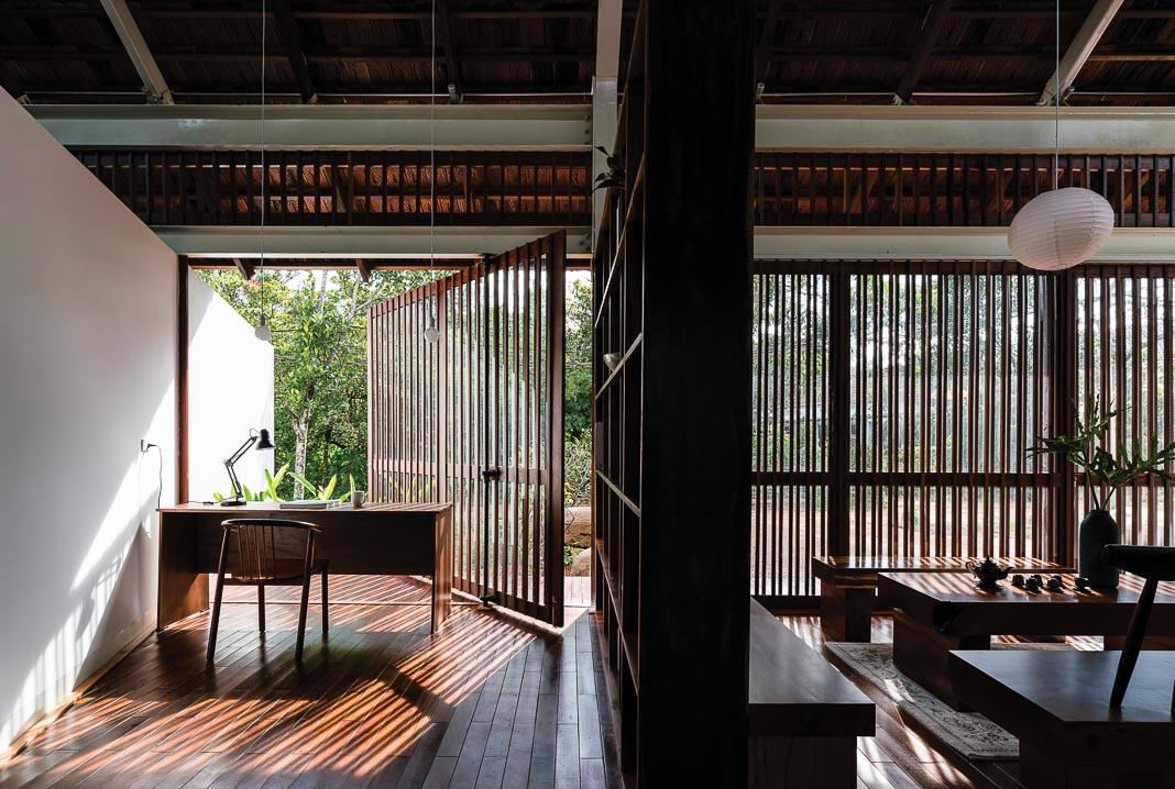 Phòng khách và góc làm việc phân chia bởi một vách ngăn nhẹ, cả hai đều có tầm nhìn ra vườn, chan hòa ánh sáng tự nhiên