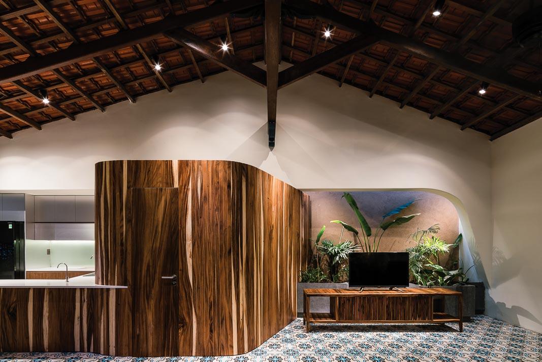 Khối gỗ giữa khu bếp và phòng khách có vai trò khá lớn, để đóng, mở và dẫn dắt cảm xúc của không gian ở nhiều thời điểm khác nhau trong ngày khi tương tác với ánh sáng và mảng xanh chung quanh 2